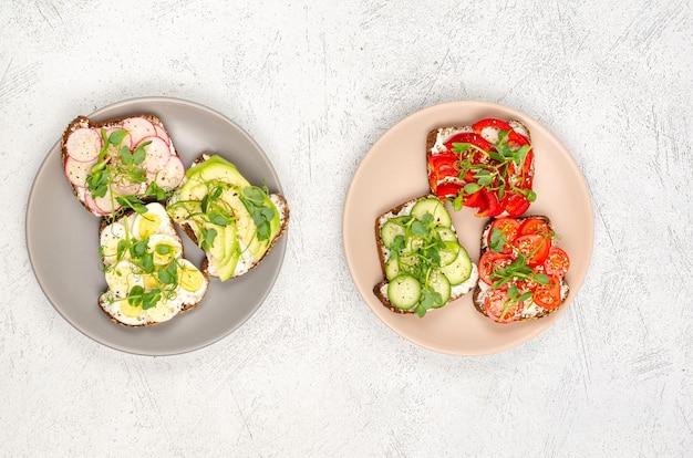 Verschiedene sandwiches mit gemüse, avacado, ei und microgreens auf tellern auf hellem hintergrund. flacher, gesunder snack. sicht von oben