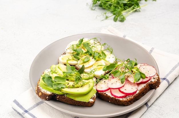 Verschiedene sandwiches mit radieschen, avacado, ei und mikrogrün auf einem grauen teller auf hellem hintergrund. flacher, gesunder snack. nahansicht.
