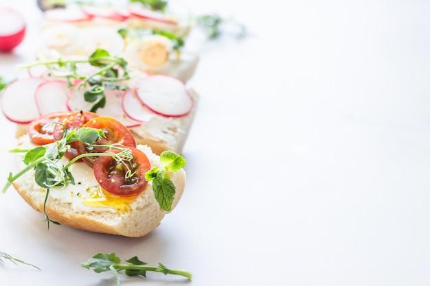 Verschiedene sandwiches mit wachteleiern, tomaten, radieschen und mikrogrün