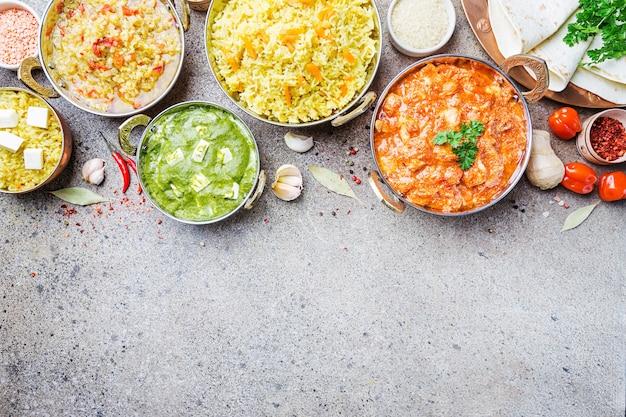 Verschiedene schalen mit verschiedenem indischem essen auf grauer steinoberfläche, draufsicht.