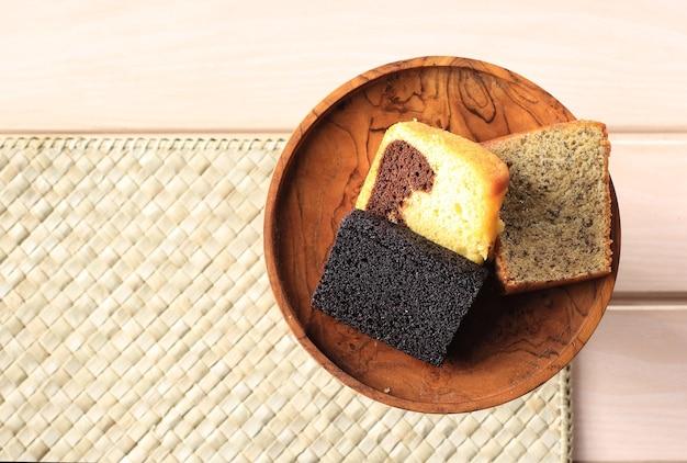 Verschiedene scheibenkuchen für indonesische snackbox. bananenkuchen, marmorkuchen und schwarzer klebreiskuchen. ansicht von oben mit textfreiraum