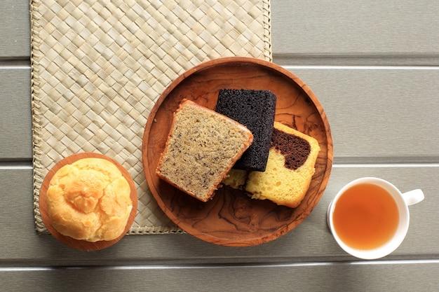 Verschiedene scheibenkuchen für snackbox. bananenkuchen, marmorkuchen und schwarzer klebreiskuchen. serviert mit tee