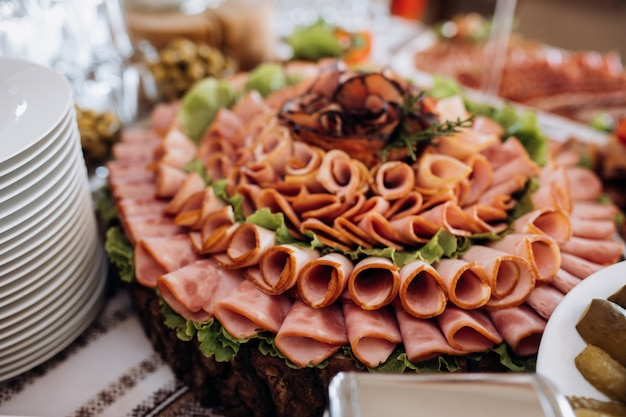 Verschiedene schinkenscheiben und mit salat dekoriert
