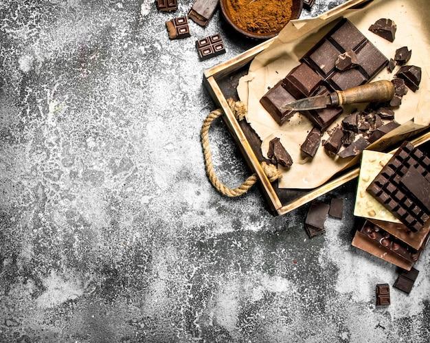 Verschiedene schokolade auf tablett auf rustikalem tisch.