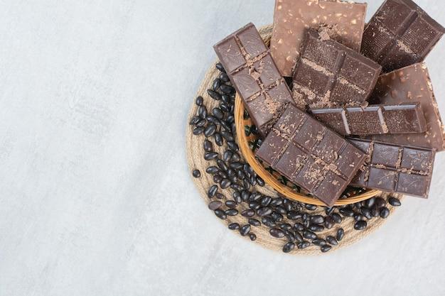 Verschiedene schokoriegel im holzkorb mit bonbons. foto in hoher qualität