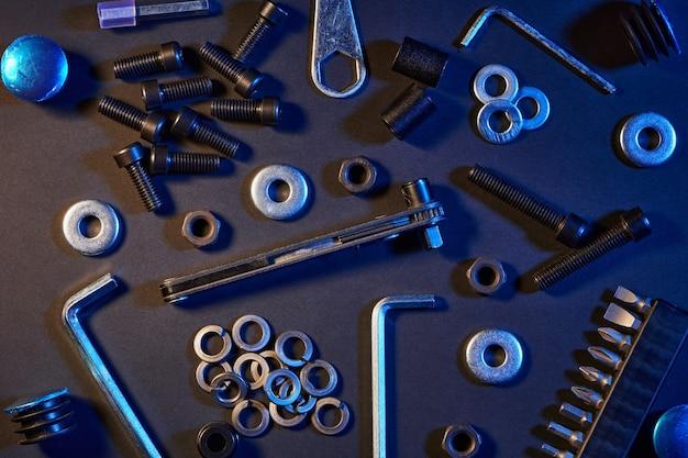 Verschiedene schrauben, muttern, unterlegscheiben, schraubendreher auf schwarzem tisch. hardware-werkzeuge und metallschrauben, muttern und unterlegscheiben.
