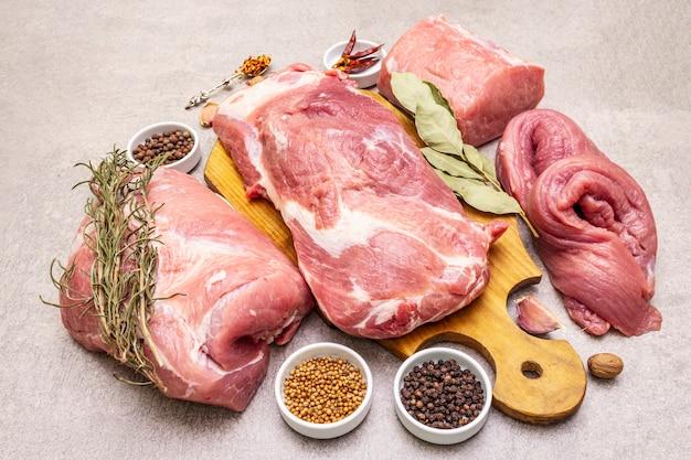 Verschiedene schweineschnitte sortiert. rohes fleisch mit gewürzen. filet, schulterblatt, hals, hinterbeinsteak