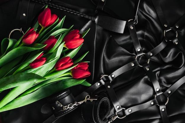Verschiedene sexspielzeuge auf schwarzem hintergrund. der blick von oben. tulpen. valentinstag