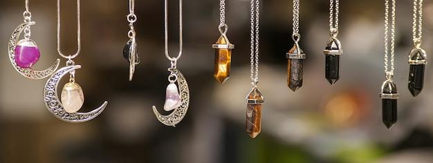 Verschiedene silberne halsketten in verschiedenen formen und farben mit farbigen steinen auf unscharfem hintergrund, bannerbild mit kopienraum