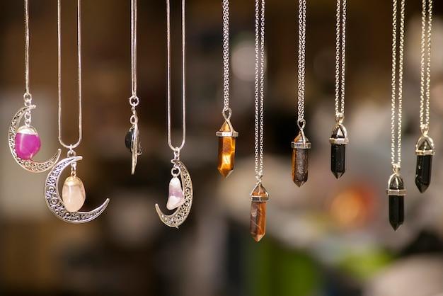 Verschiedene silberne halsketten in verschiedenen formen und farben mit farbigen steinen auf unscharfem hintergrund