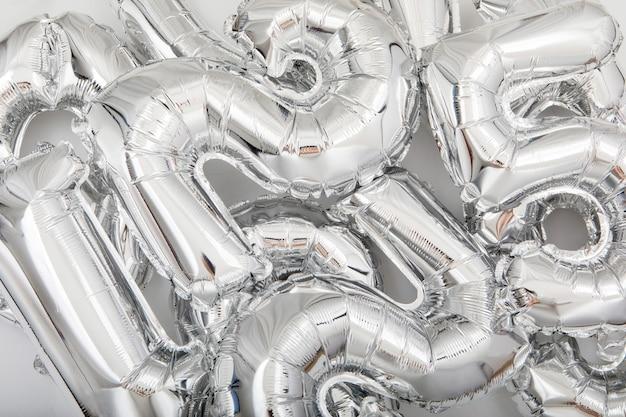 Verschiedene silberne luftballons auf weißem hintergrund