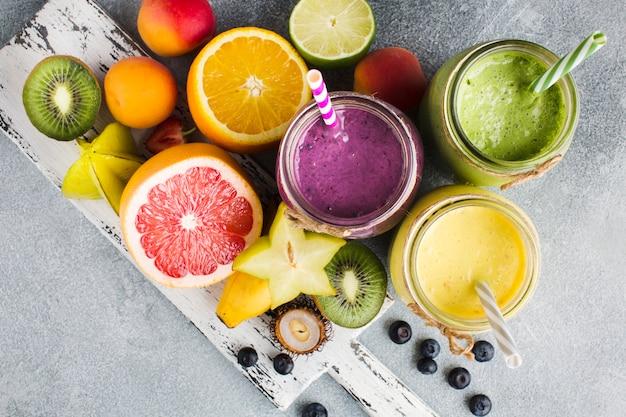 Verschiedene smoothie-gläser mit zutaten