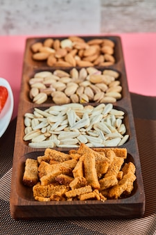 Verschiedene snacks auf dem rosa tisch. pistazien, sonnenblumenkerne, mandeln, cracker.
