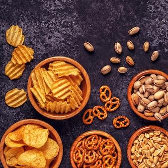 Verschiedene snacks in schalen mit kartoffelchips, nüssen und brezeln