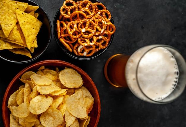 Verschiedene snacks in schalen und ein bier auf dem tisch