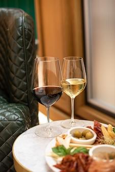 Verschiedene snacks. käsevorspeise, wurstwaren, oliven mit zwei gläsern rot- und weißwein im restaurant oder café.