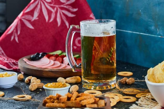 Verschiedene snacks, pommes, ein teller mit würstchen und ein glas bier auf dunkler oberfläche.