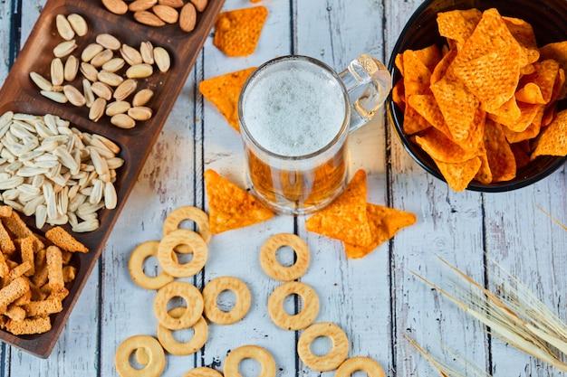 Verschiedene snacks, pommes und bier auf blauem tisch. tisch für eine gruppe von freunden.