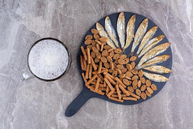 Verschiedene snacks und ein glas bier auf marmoroberfläche. foto in hoher qualität