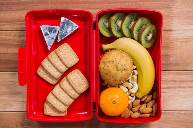 Verschiedene snacks und obst in lunchbox