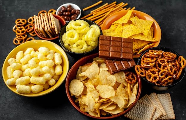 Verschiedene snacks und schokolade auf einem schwarzen tisch