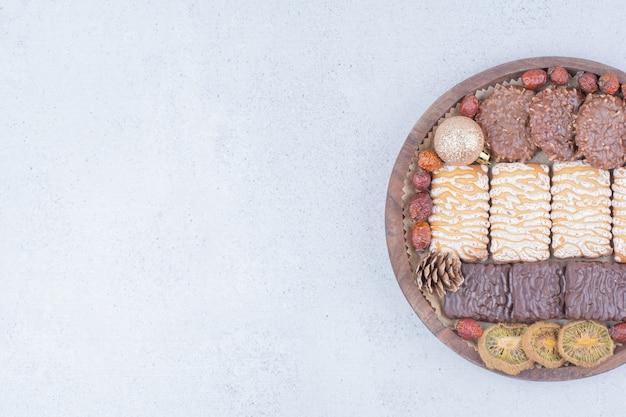 Verschiedene snacks und weihnachtskugeln auf holzbrett.