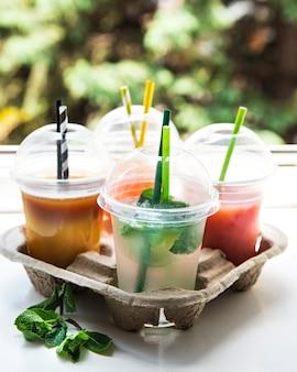 Verschiedene sommerliche kalte getränke und cocktails in einem papierhalter