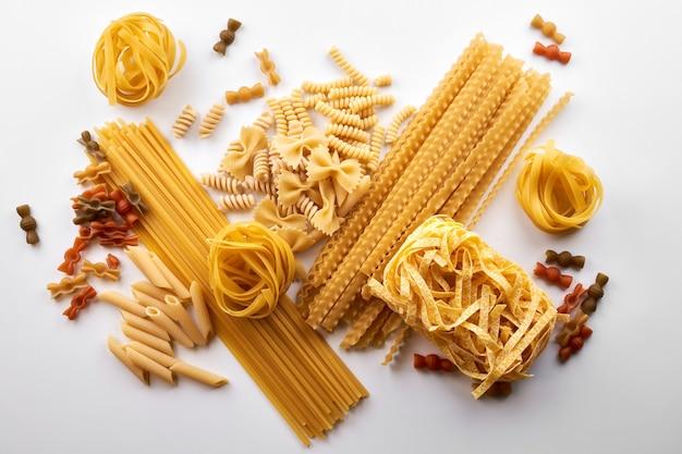 Verschiedene sorten von nudeltapeten. mischen sie makkaroni, spaghetti auf weißem hintergrund