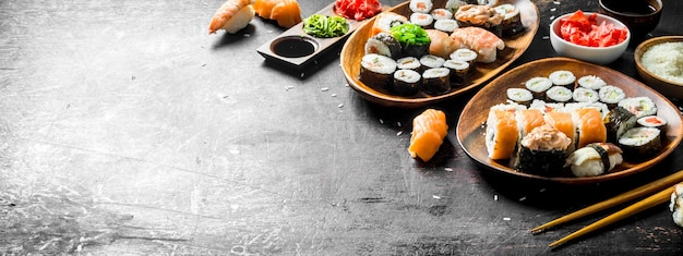 Verschiedene sorten von sushi, brötchen und maki auf den tellern. auf dunklem rustikalem hintergrund
