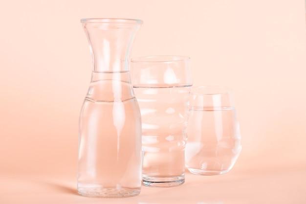Verschiedene sortierte gläser mit wasser- und pfirsichhintergrund