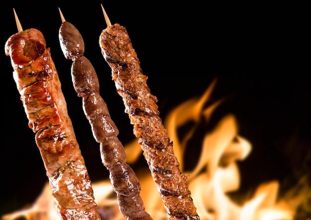 Verschiedene steakspieße über feuerflammen.