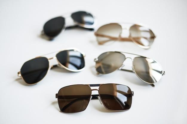 Verschiedene stilvolle modische sonnenbrillen lokalisiert auf weißem hintergrund
