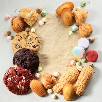 Verschiedene süße backwaren/gebäck mit textfreiraum auf weißem marmortisch für text oder rezept. makronen, baiser, madeleine, craquelin eclair, mini-croissant, big cookies. ansicht von oben