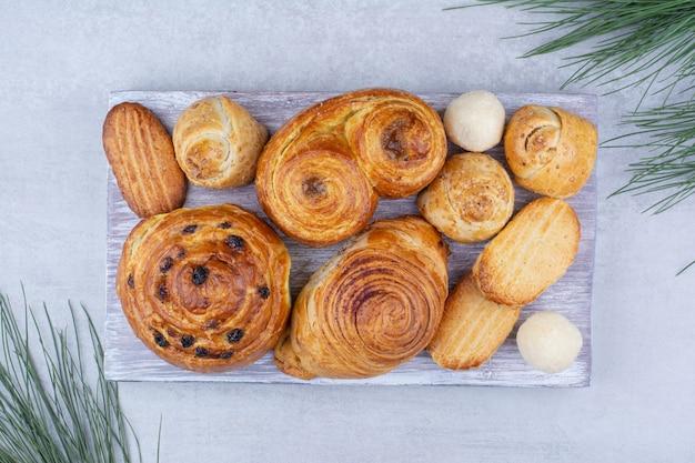 Verschiedene süße backwaren und brötchen mit keksen auf holzbrett.