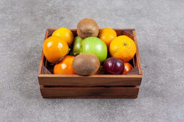 Verschiedene süße frische früchte auf einem holzkorb