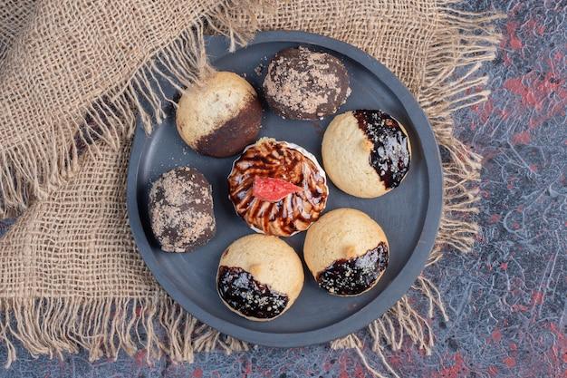 Verschiedene süße kekse auf schwarzem teller