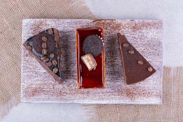 Verschiedene süße kuchen auf holzbrett mit sackleinen. foto in hoher qualität