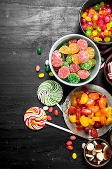Verschiedene süße süßigkeiten, gelee und kandiert in einer schüssel. auf der schwarzen tafel.