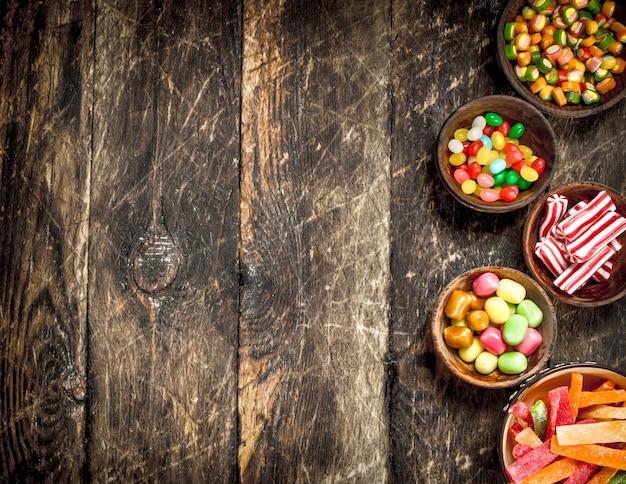 Verschiedene süße süßigkeiten in schalen. auf einem hölzernen hintergrund.