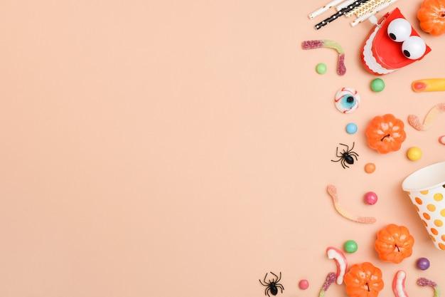 Verschiedene süßigkeiten auf einem orangefarbenen hintergrund auf der rechten seite des hintergrunds mit platz für text. hintergrund für den halloween-urlaub.