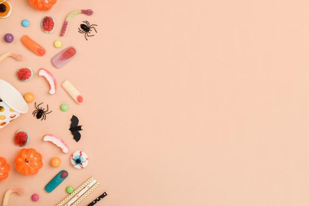 Verschiedene süßigkeiten auf orange im linken teil des hintergrunds mit platz für text. hintergrund für den halloween-urlaub. flaches layout, draufsicht, ein ort zum kopieren.