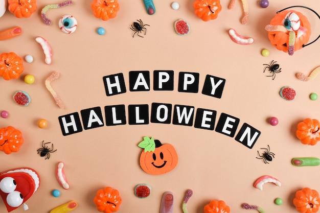Verschiedene süßigkeiten auf orangefarbenem hintergrund mit platz für text. fröhliches halloween.