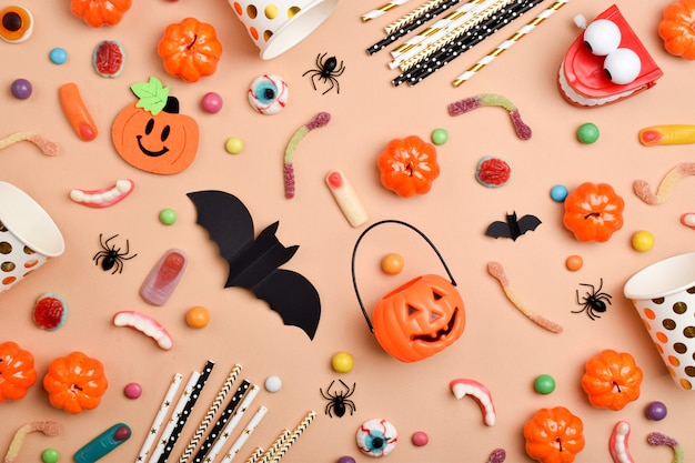 Verschiedene süßigkeiten auf orangefarbenem hintergrund mit platz für text. hintergrund für den halloween-urlaub. flacher grundriss, draufsicht