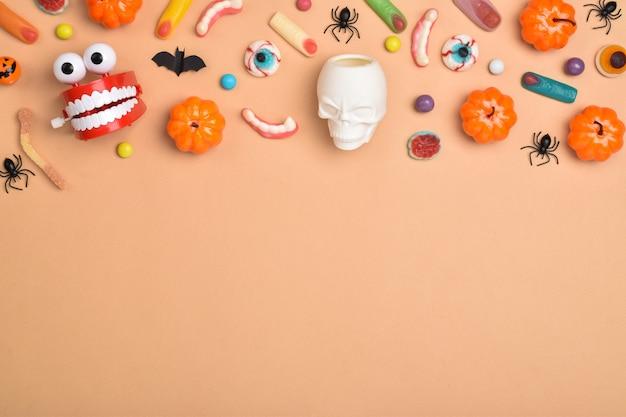 Verschiedene süßigkeiten auf orangefarbenem hintergrund mit platz für text. hintergrund für den halloween-urlaub. flaches layout, draufsicht, ein ort zum kopieren. fröhliches halloween.
