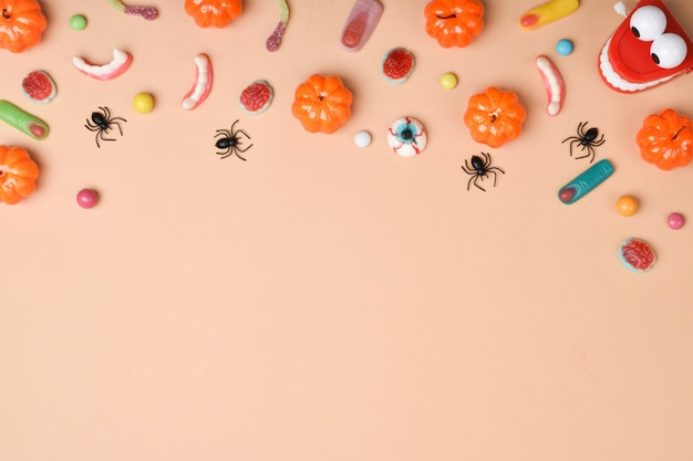 Verschiedene süßigkeiten auf orangefarbenem hintergrund mit platz für text. hintergrund für den halloween-urlaub. flaches layout, draufsicht, ein ort zum kopieren.