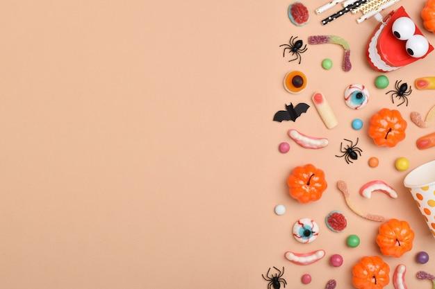 Verschiedene süßigkeiten auf orangefarbenem hintergrund mit platz für text. hintergrund für den halloween-urlaub.