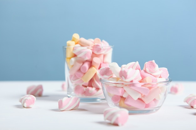 Verschiedene süßigkeiten und süßigkeiten auf dem tisch auf farbigem hintergrund