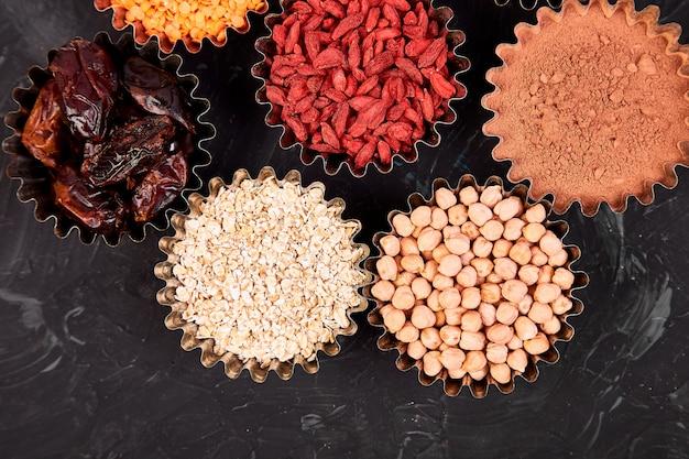 Verschiedene superfoods im schälchen auf schwarz