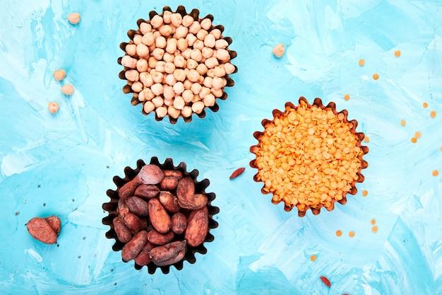 Verschiedene superfoods in der kleinen schüssel auf blauem hintergrund