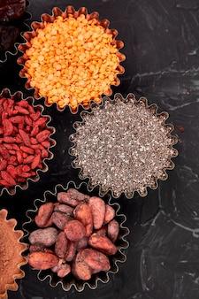 Verschiedene superfoods in der kleinen schüssel auf schwarzem hintergrund